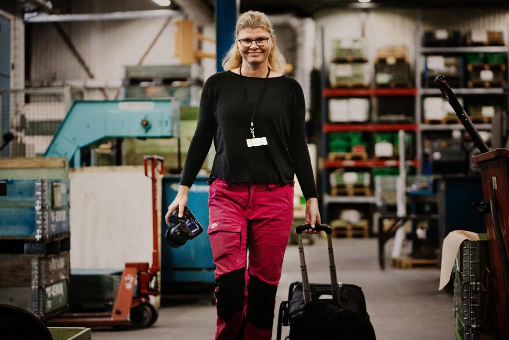 Fotograf bilder Industrifotografering Tjej med kamera väska går i en industri lokal