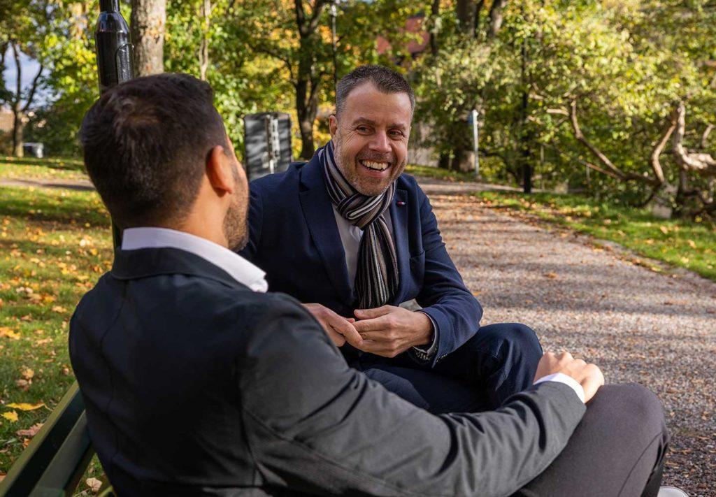 Två manliga doktorer sitter på en park bänk bildbank