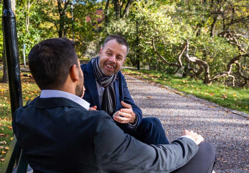 Två manliga doktorer sitter på en park bänk
