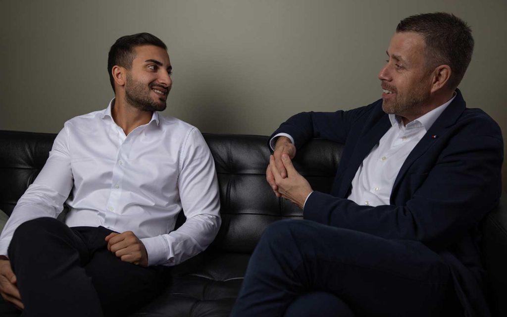 Två manliga doktorer sitter i en soffa
