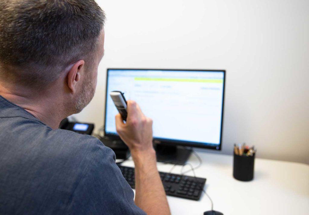EN manlig doktor dikterar in i sin diktafon